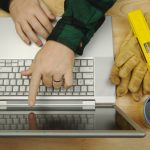 Contractor Researches on Laptop with paint brush roller and wood stir stick by his side. Great image for online information regarding home improvement additions and remodeling.